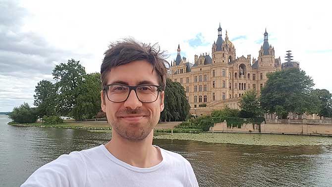 Ich vor dem Schloss auf der Suche nach guten Restaurants in Schwerin